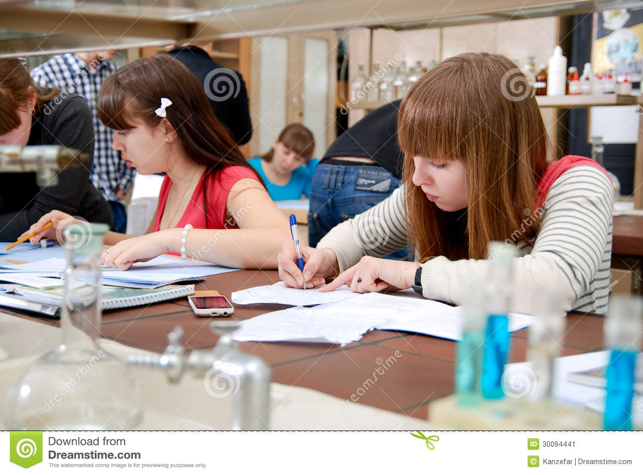 Students at work in the laboratory of chemistry take notes in a