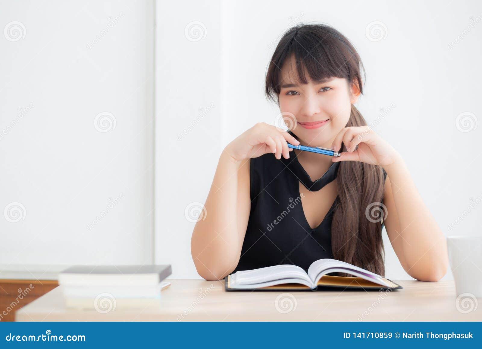 Studio di seduta sorridente della bella donna asiatica del ritratto giovane ed imparare scrivendo taccuino e diario nel salone a