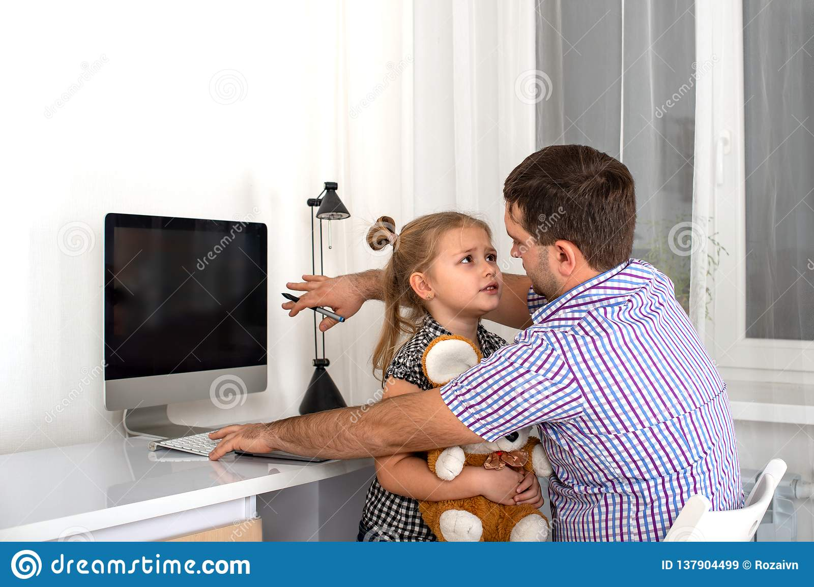 Studio emotional shot of a young girl asking a busy person computer dad give her attention and play with her
