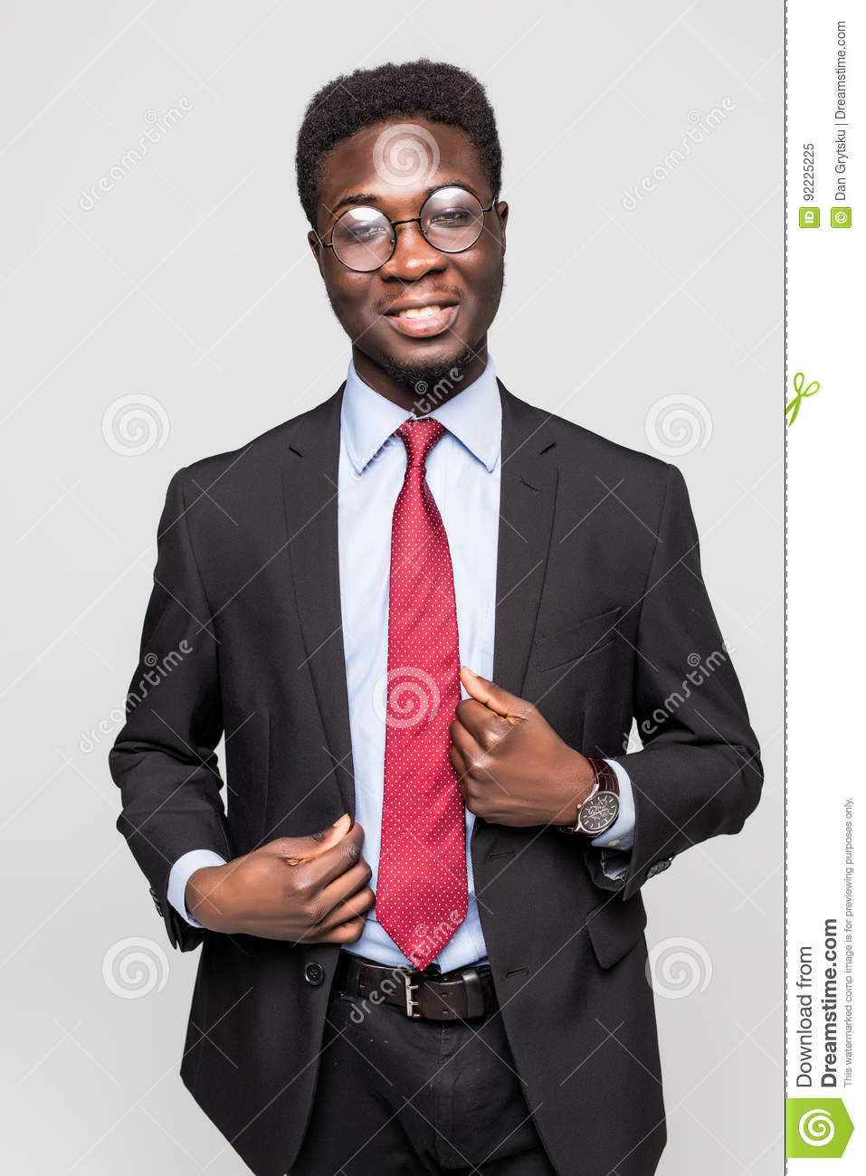 Studio fashion portrait of a handsome young African American businessman wearing a black suit and tie. Isolated on gray background