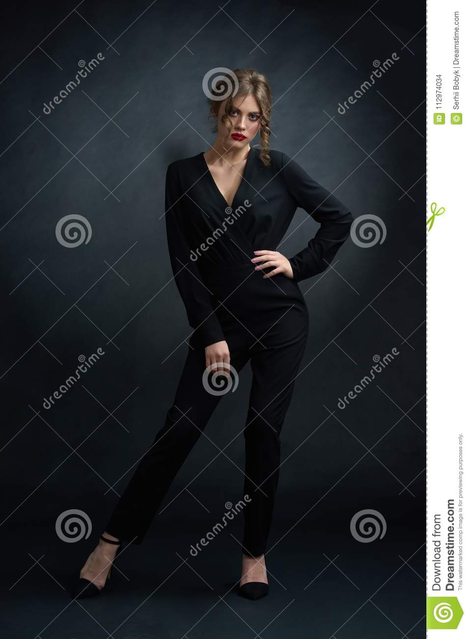 Studio frontview of confident woman wearing black suit.