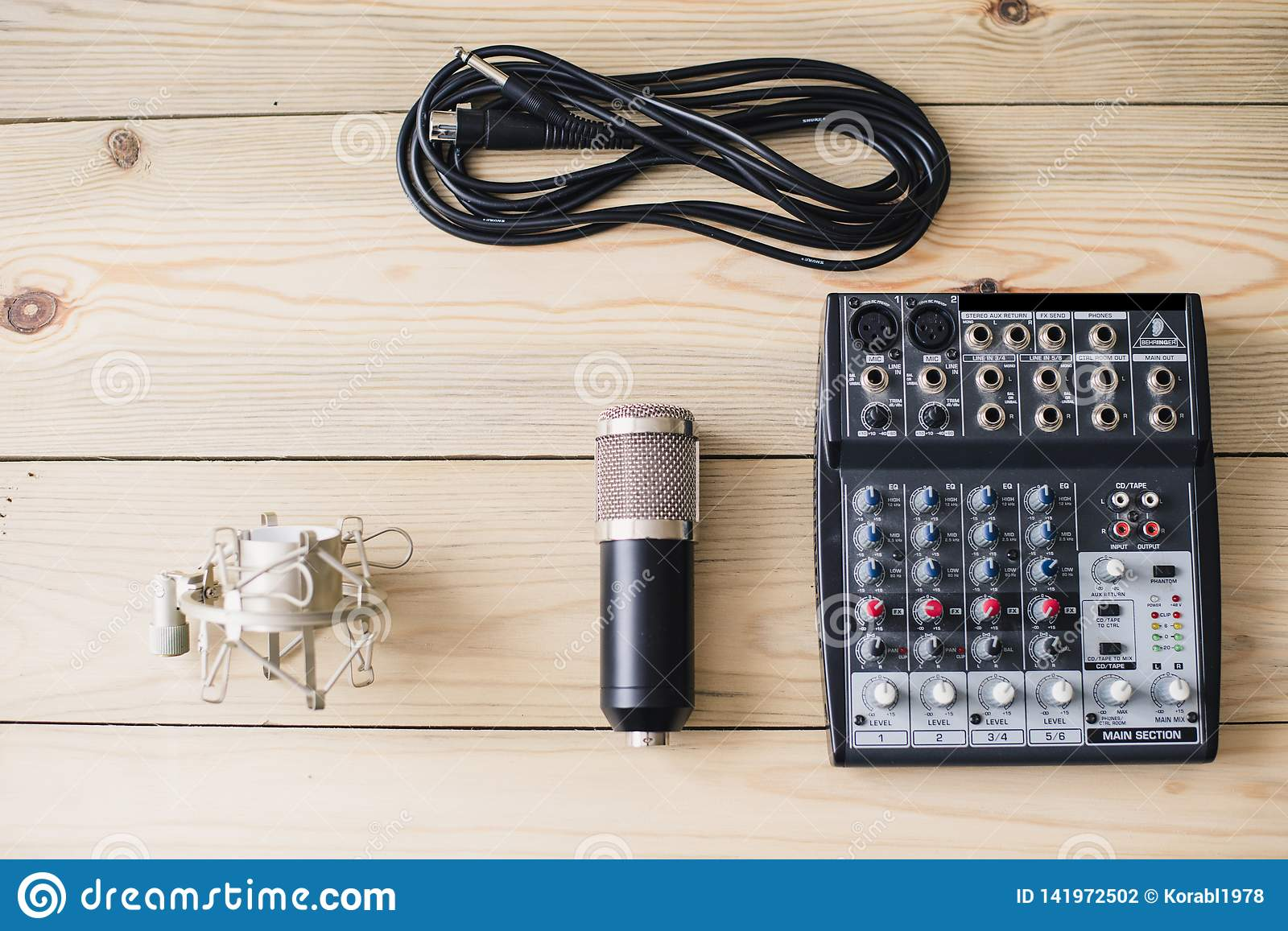 Studio laptop microphone and mixing console on wooden background