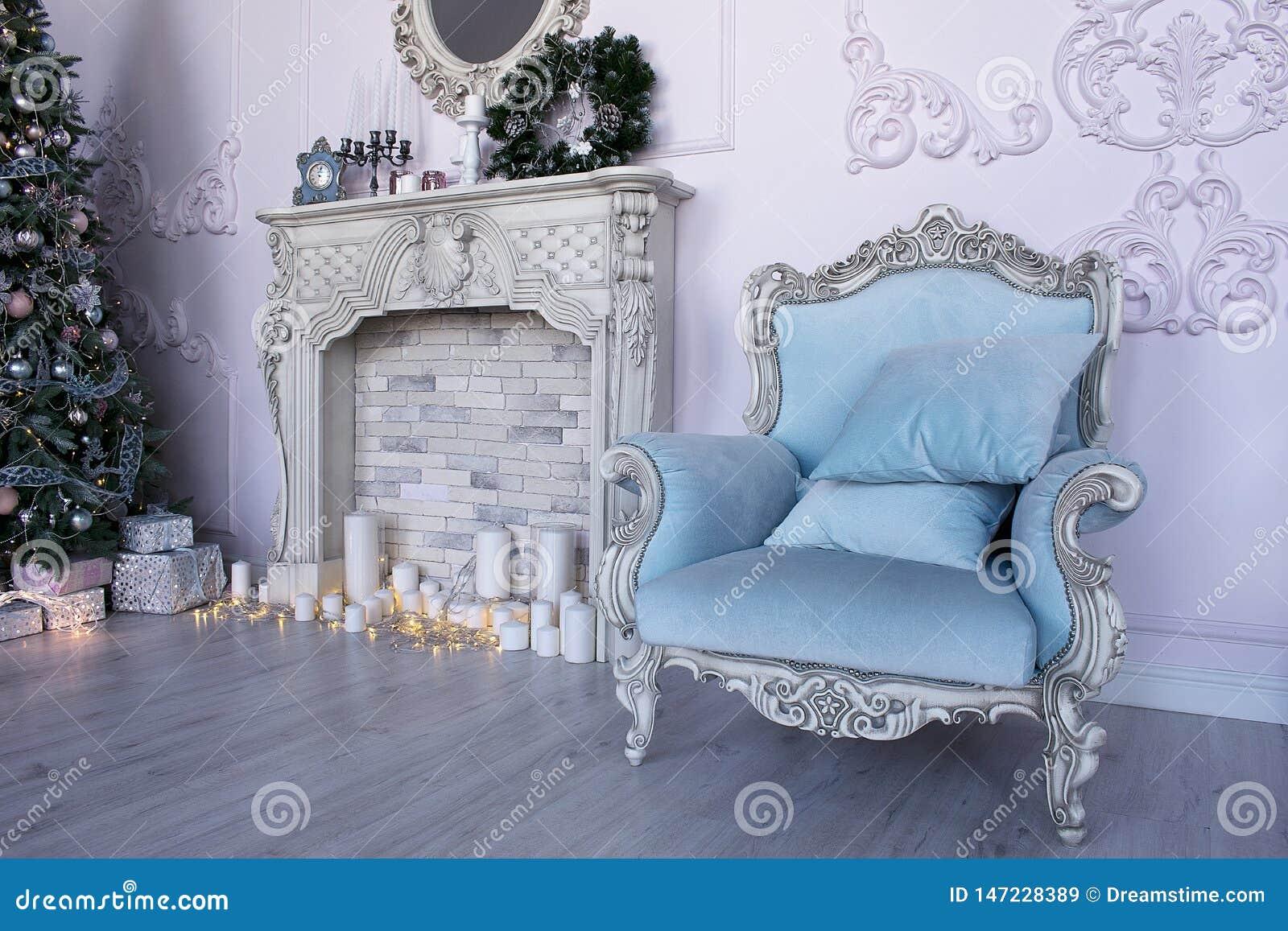 Studio mit einem blauen Lehnsessel, einem Kamin und einem Weihnachtsbaum
