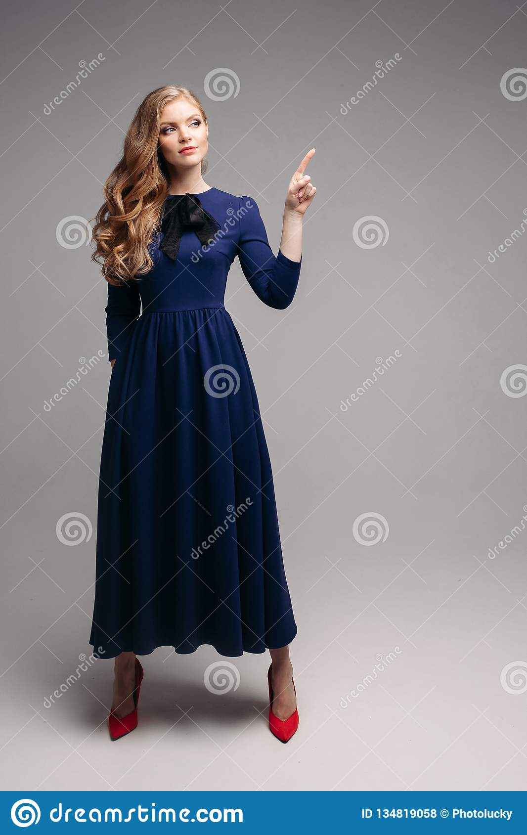 f19b9d5b2ff Studio portrait of attractive woman with long wavy hair in tail wearing  dress and black high heels over white background. Isolate.