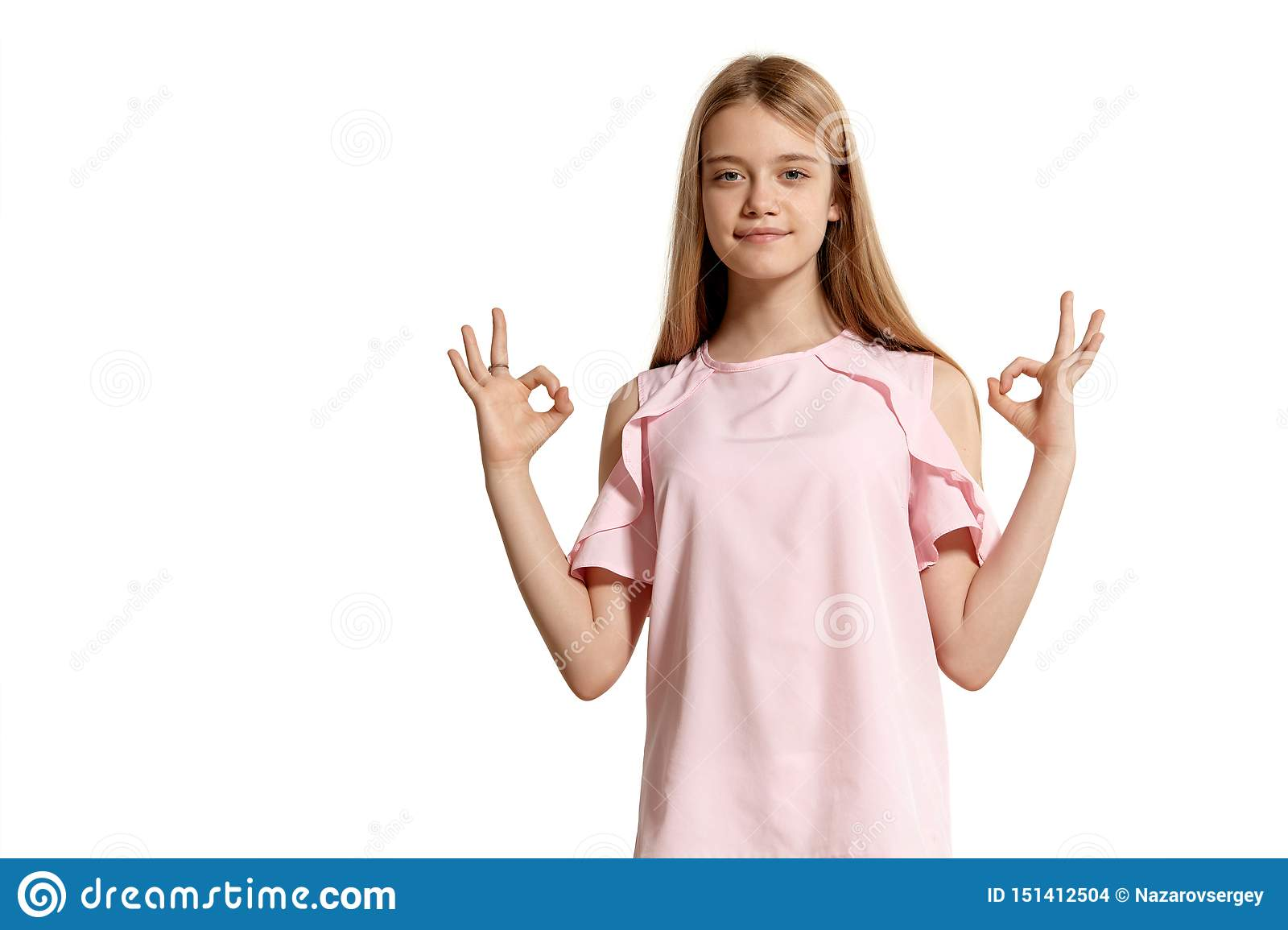 Studio portrait of a beautiful girl blonde teenager in a pink t-shirt posing isolated on white background.