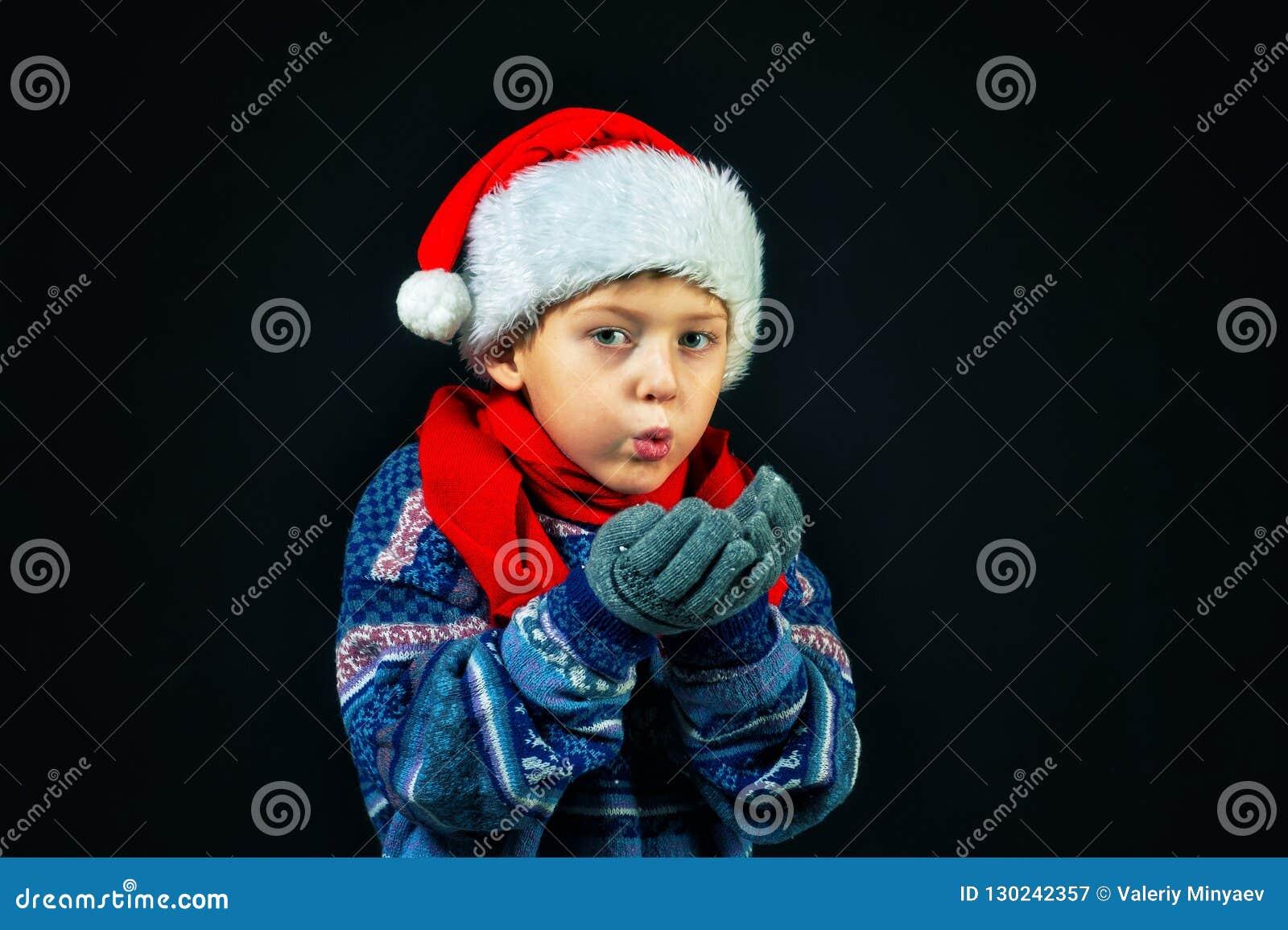 Studio portrait of a cheerful boy in Santa`s hat
