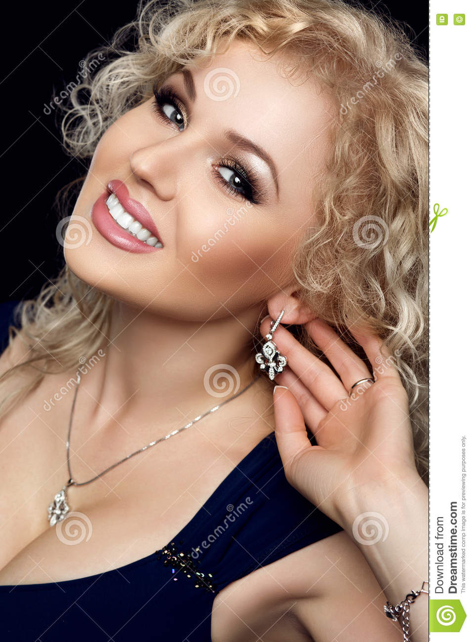 Studio portrait of gorgeous blonde woman smiling, darling necklace on her neck, earrings with precious stones touched by