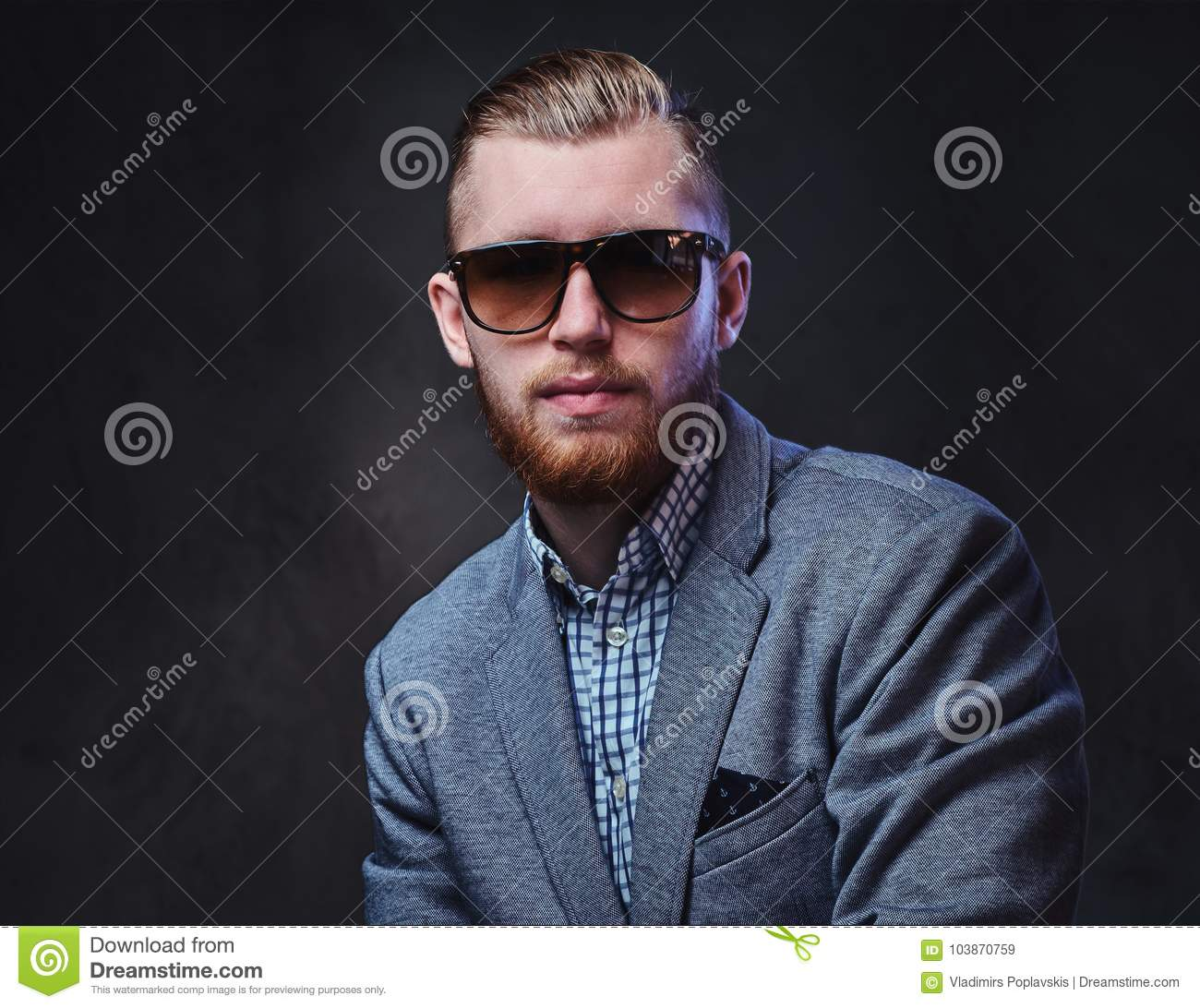 1819e584064f Studio portrait of redhead bearded male dressed in a suit and sunglasses  over grey background.