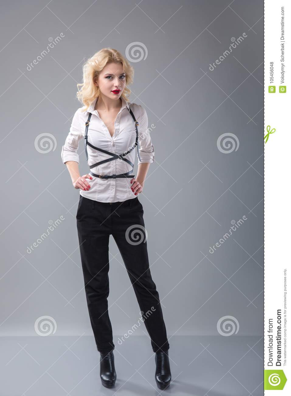 f2b01924e Studio portrait of a young blonde woman wearing white shirt with suspenders  or belts over grey background