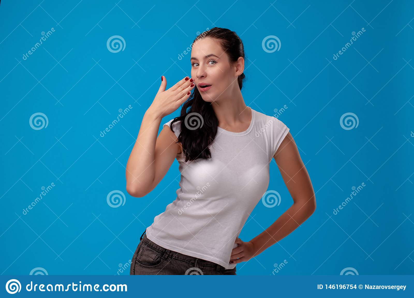 Studio portrait of a young beautiful woman in a white t-shirt against a blue wall background. People sincere emotions.