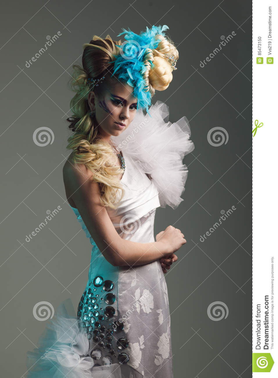 Studio shoot of woman with creative hairstyle, makeup and dress.