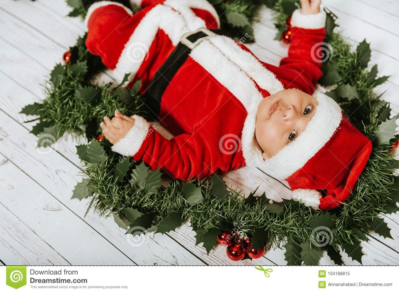 678982a80472 Studio shot of adorable baby boy wearing Santa Claus` outfit, lying on white  background in Christmas decoration, top view