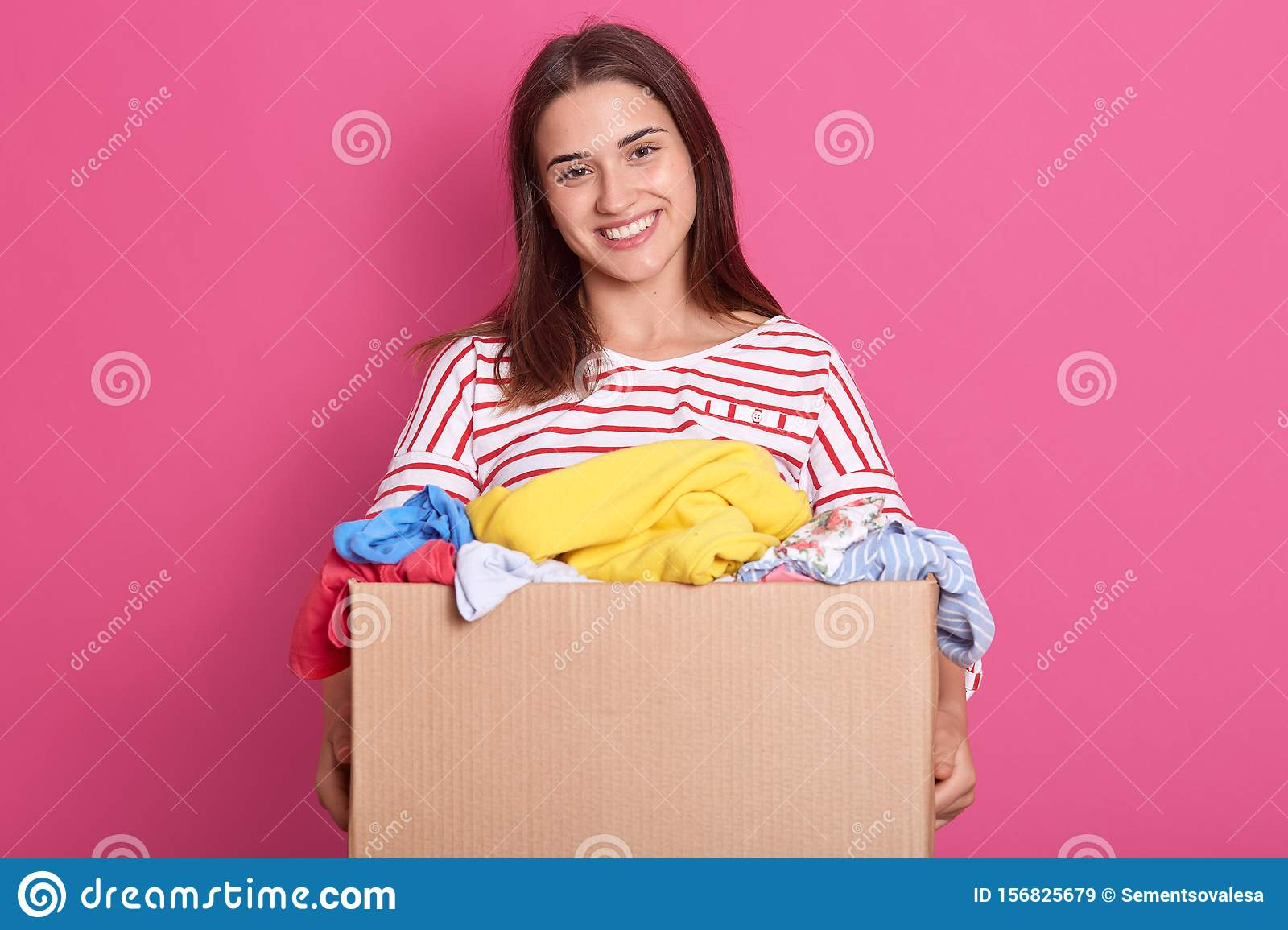 Studio shot of adorable female stands smiling with box full of reusable clothing for poor people isolated over pink background,