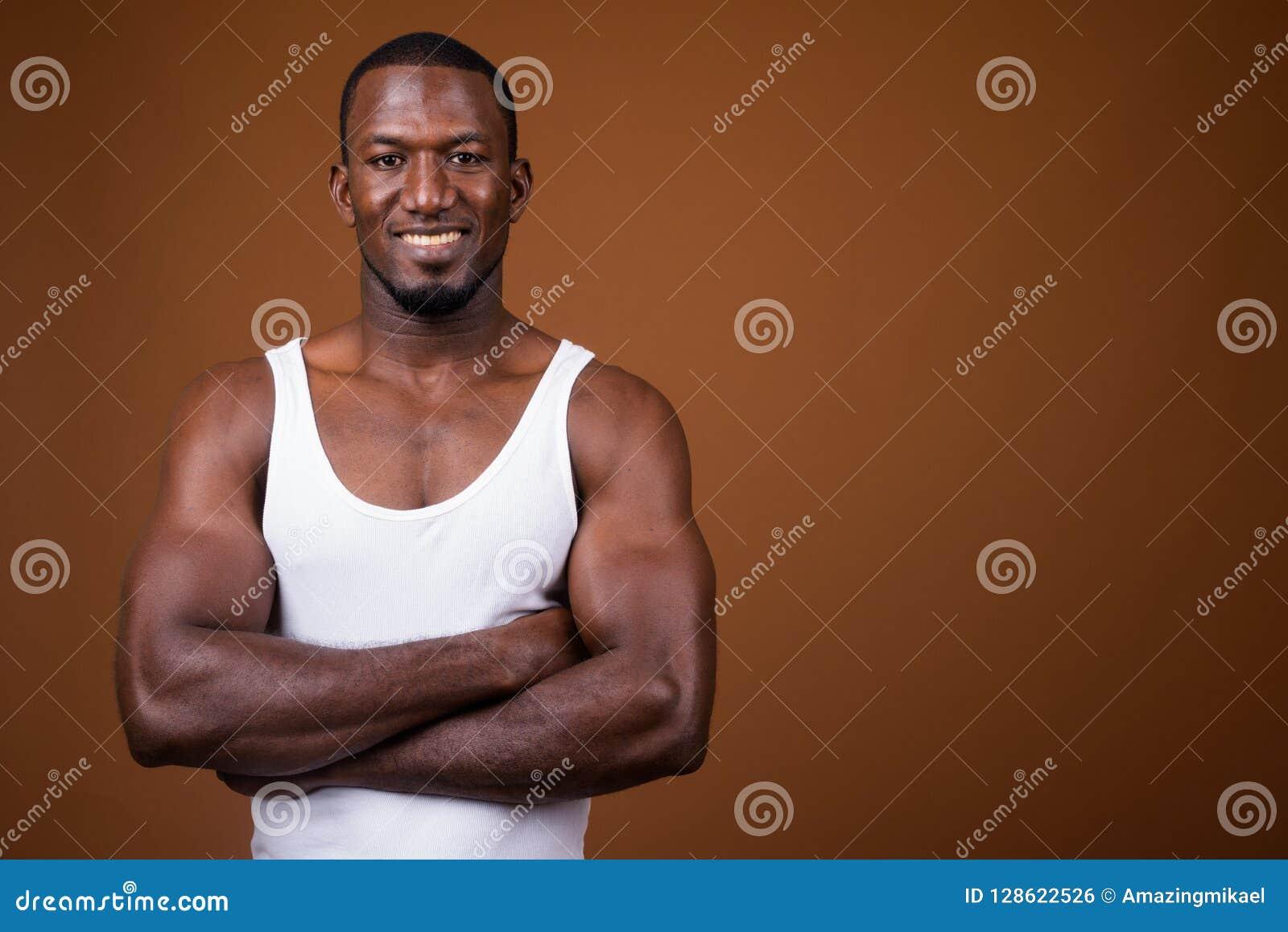 3625fffae Studio shot of handsome muscular African man wearing tank top against brown  background