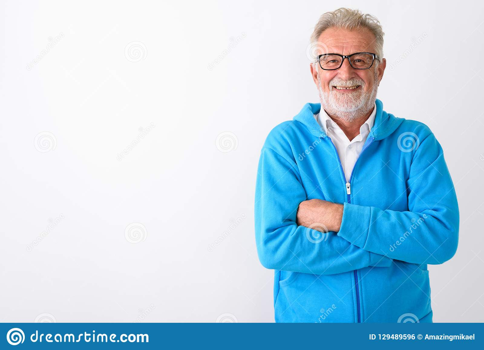 Studio shot of happy senior bearded man smiling with arms crosse