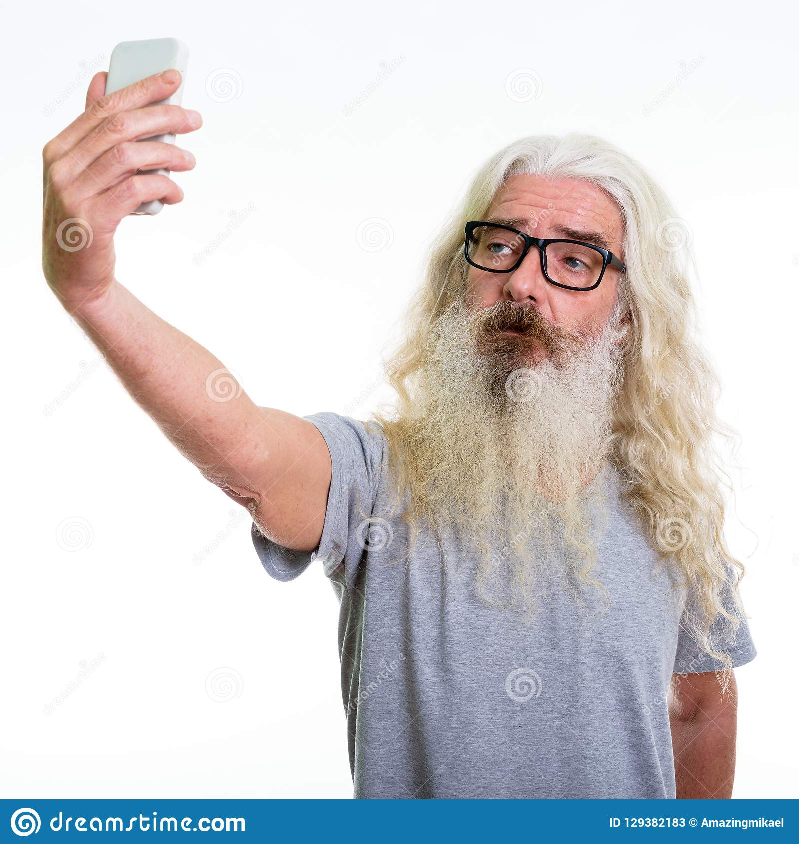 Studio shot of senior bearded man taking selfie picture with mob