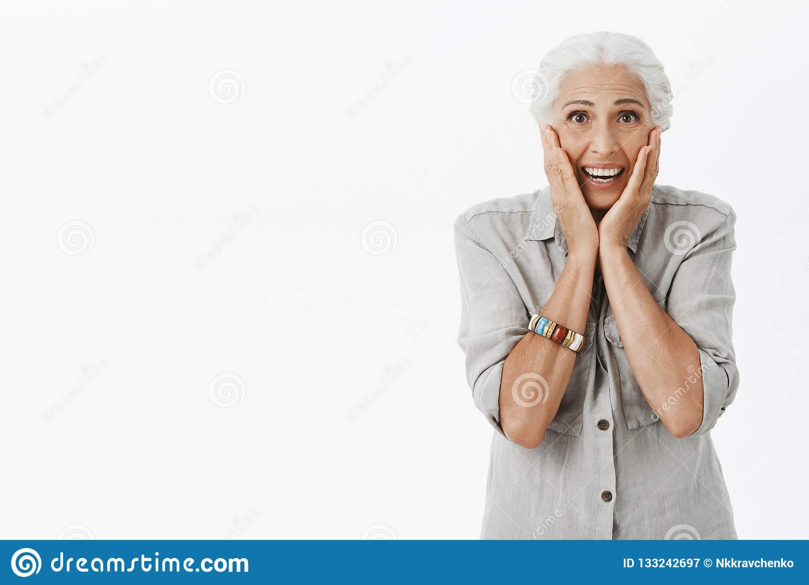 Studio shot of senior woman reacting on surprise. Portrait of touched and delighted cute old lady with white hair