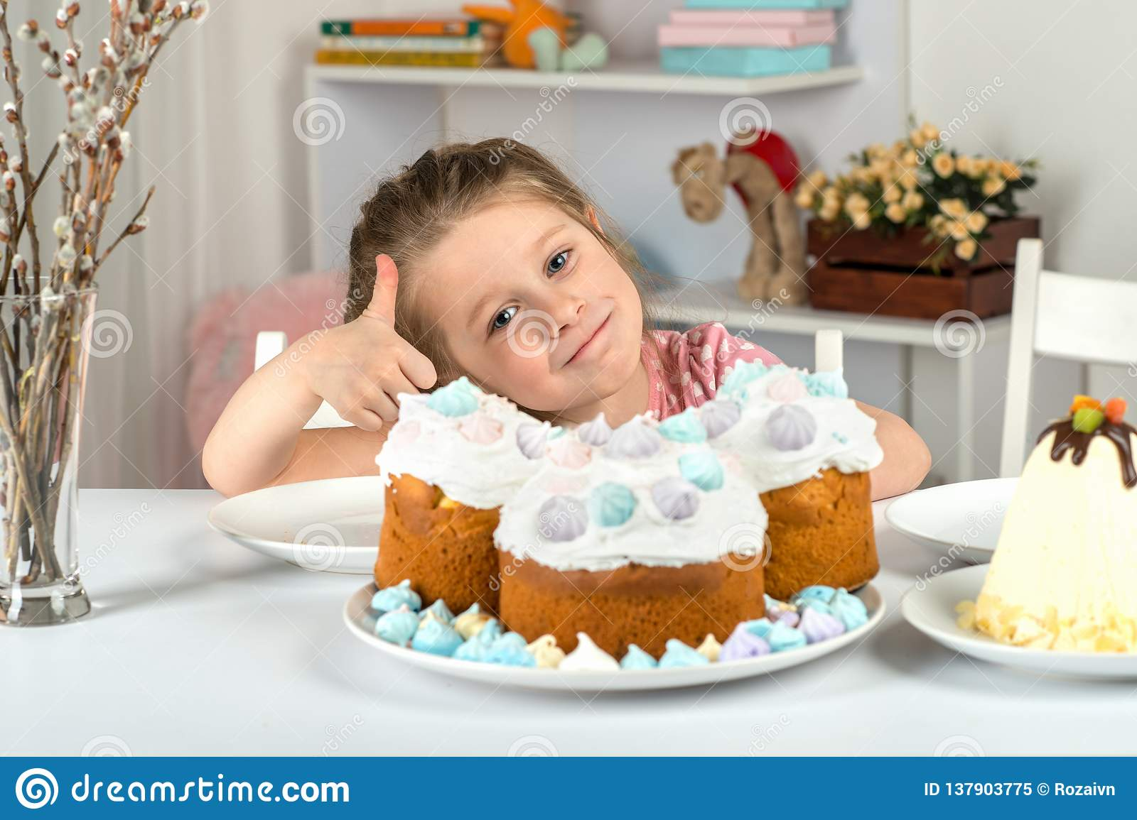 Studio shot of little girl sitting at a table with Easter cakes. She shows thumb up gesture that Easter cake is very tasty