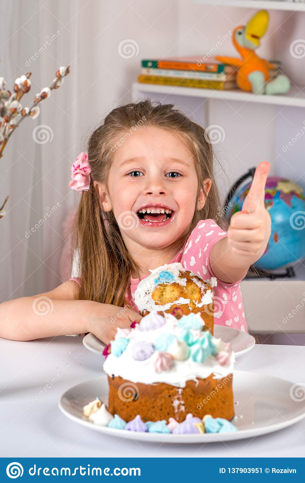 Studio shot of small girl sitting at a table and eating Easter . She have a festive mood and gestures a sign of approval
