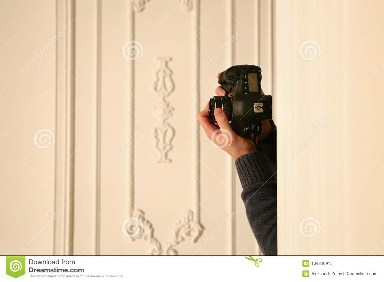 Studio shot of somebody hands behind the wall holding professional photocamera