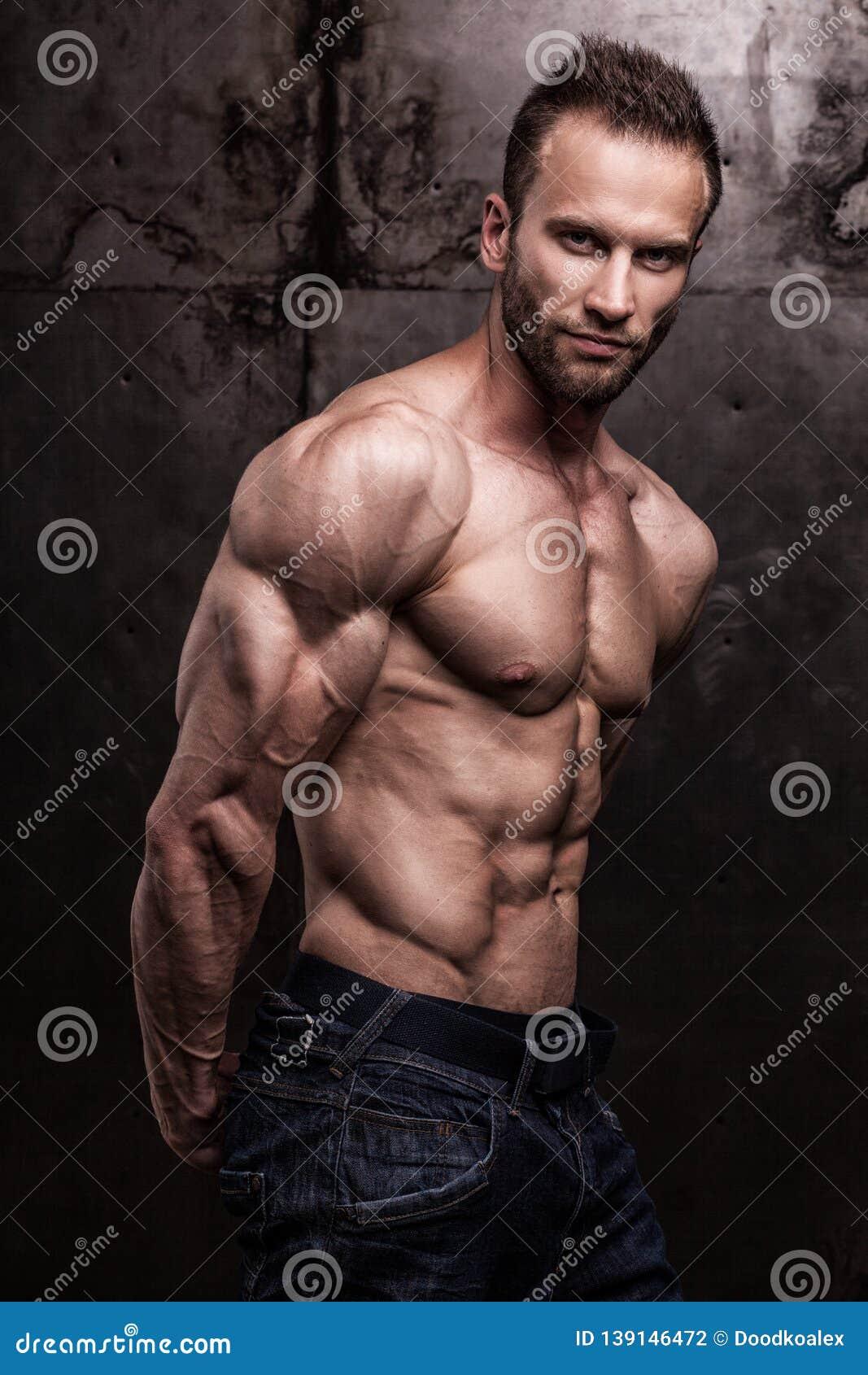 Strong athletic man on dark grunge background