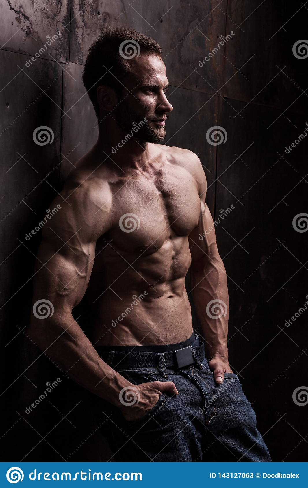Strong athletic man on dark grunge background