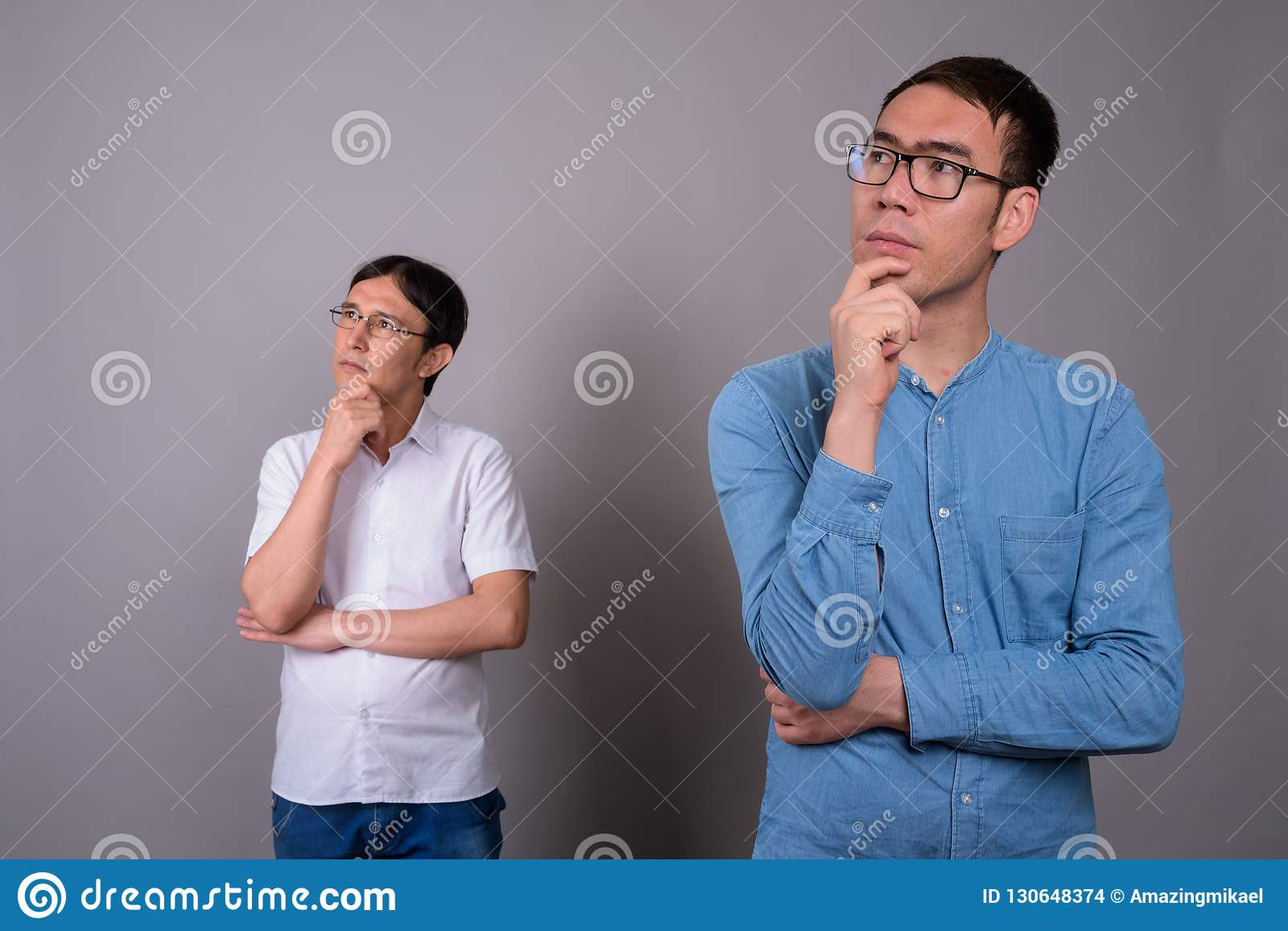 Two young Asian businessmen wearing eyeglasses together against