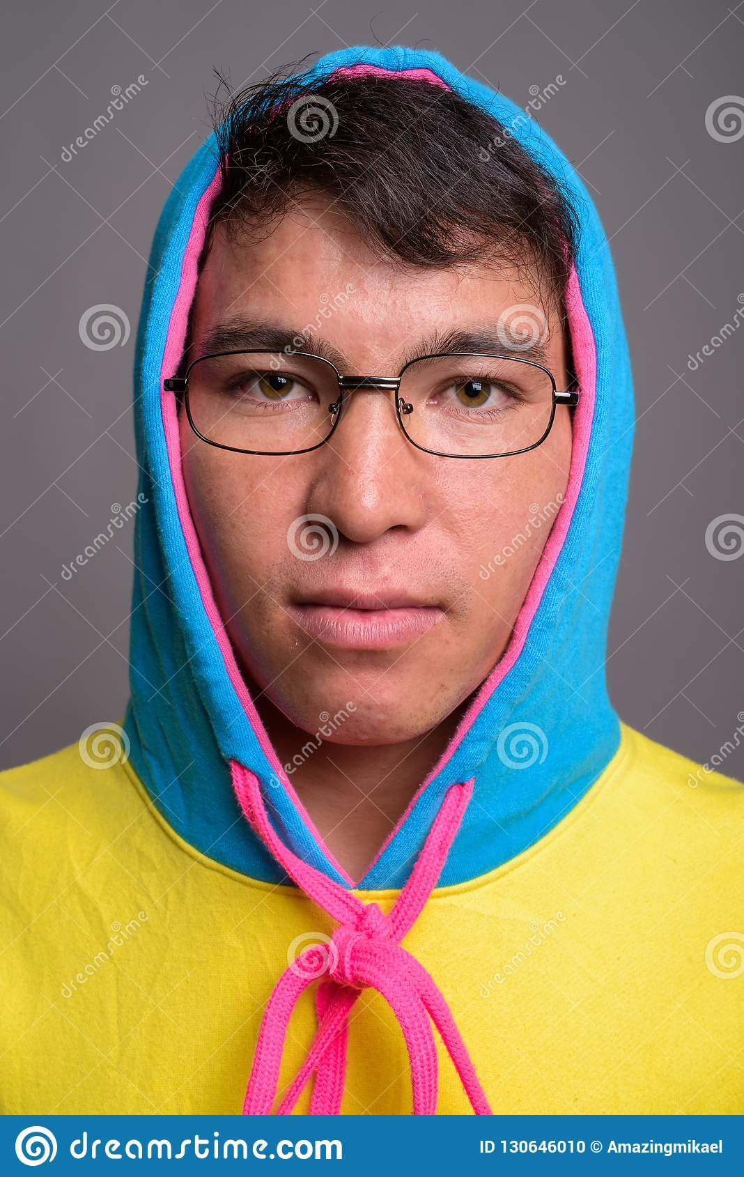 Young Asian man wearing colorful hoodie and eyeglasses against g