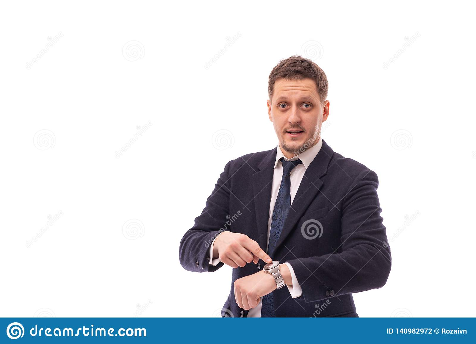 Studio shot of a young businessman wearing dark blue suit points to time on a wristwatch recalling the necessary discipline or