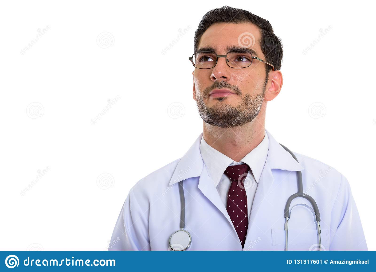 Studio shot of young handsome man doctor thinking while looking