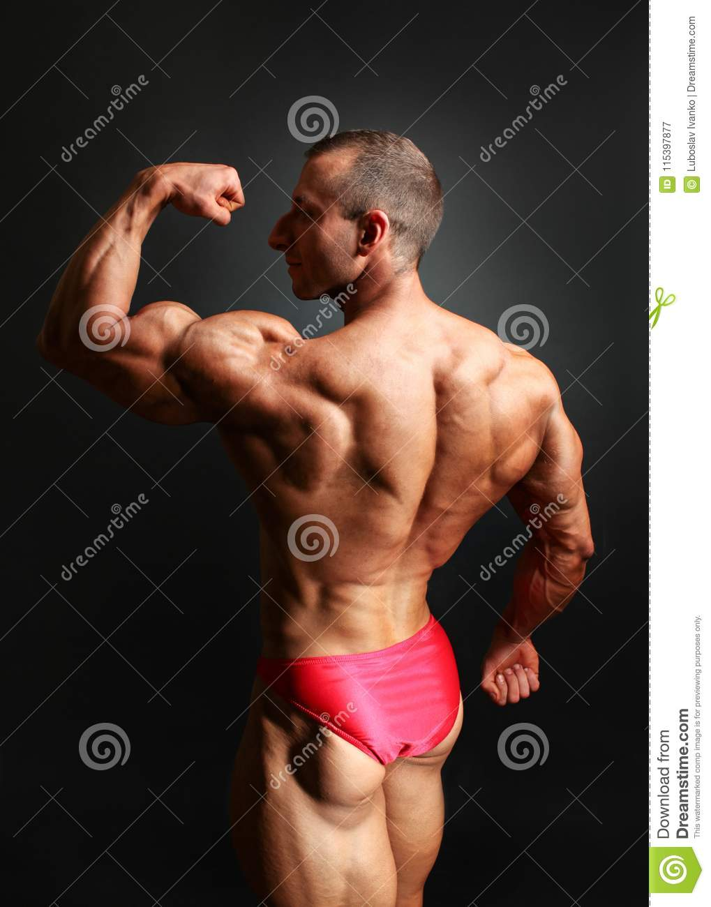 Studio shot of young male bodybuilder posing, showing his biceps