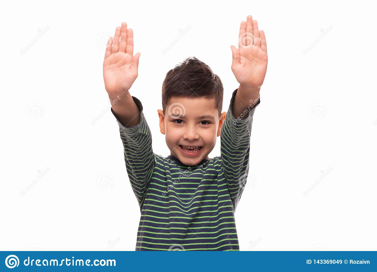 Studio shot of a young smiling boy wearing green striped shirt standing with his hands raised, isolated with copy space