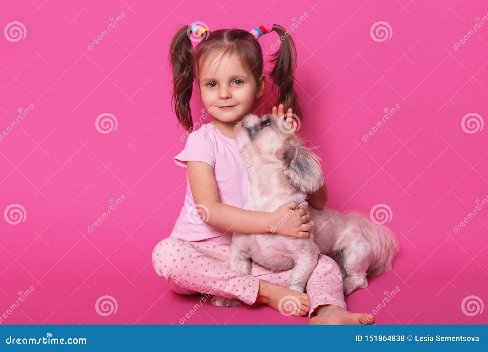Studio sparato di poco bambino divertente che si siede sul pavimento, esaminando direttamente la macchina fotografica, abbraccian