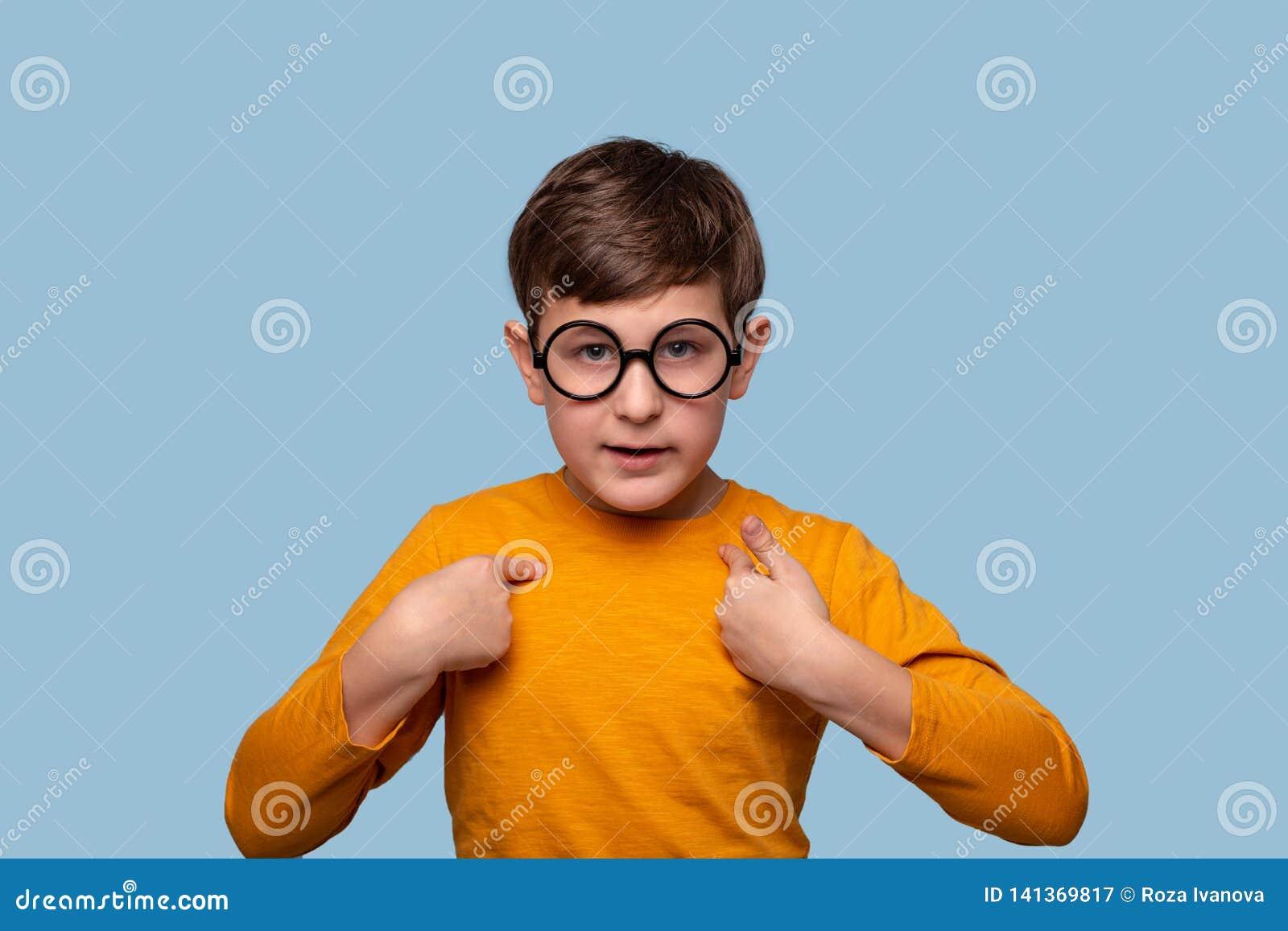 Studio strzał poważna chłopiec udowadnia coś wskazuje jego ręki on, odizolowywający na błękicie z kopii przestrzenią