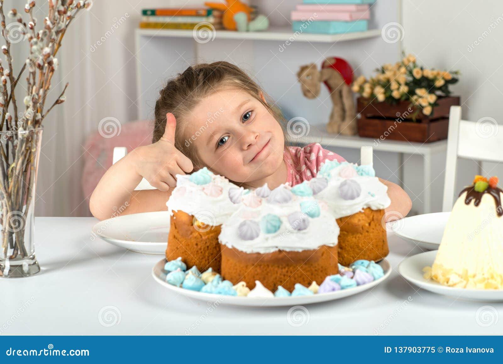 Studio strzał małej dziewczynki obsiadanie przy stołem z Wielkanocnymi tortami Pokazuje kciuk w górę gesta że wielkanoc tort jest