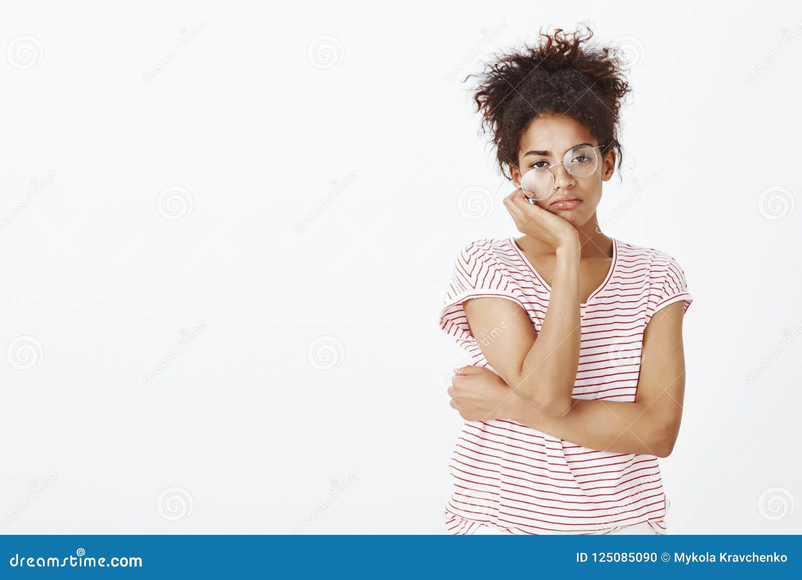 Studio strzał zanudzająca nieszezególna śliczna córka w pasiastej koszulce i szkłach, patrzeje z niestarannym wyrażeniem przy