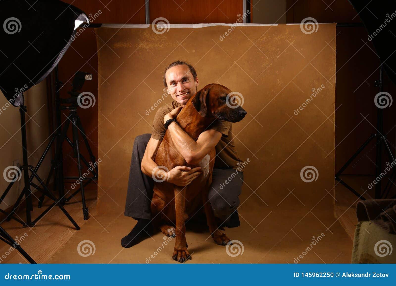 Studio strza? m??czyzna z Rhodesian Ridgeback psem na br?zu tle