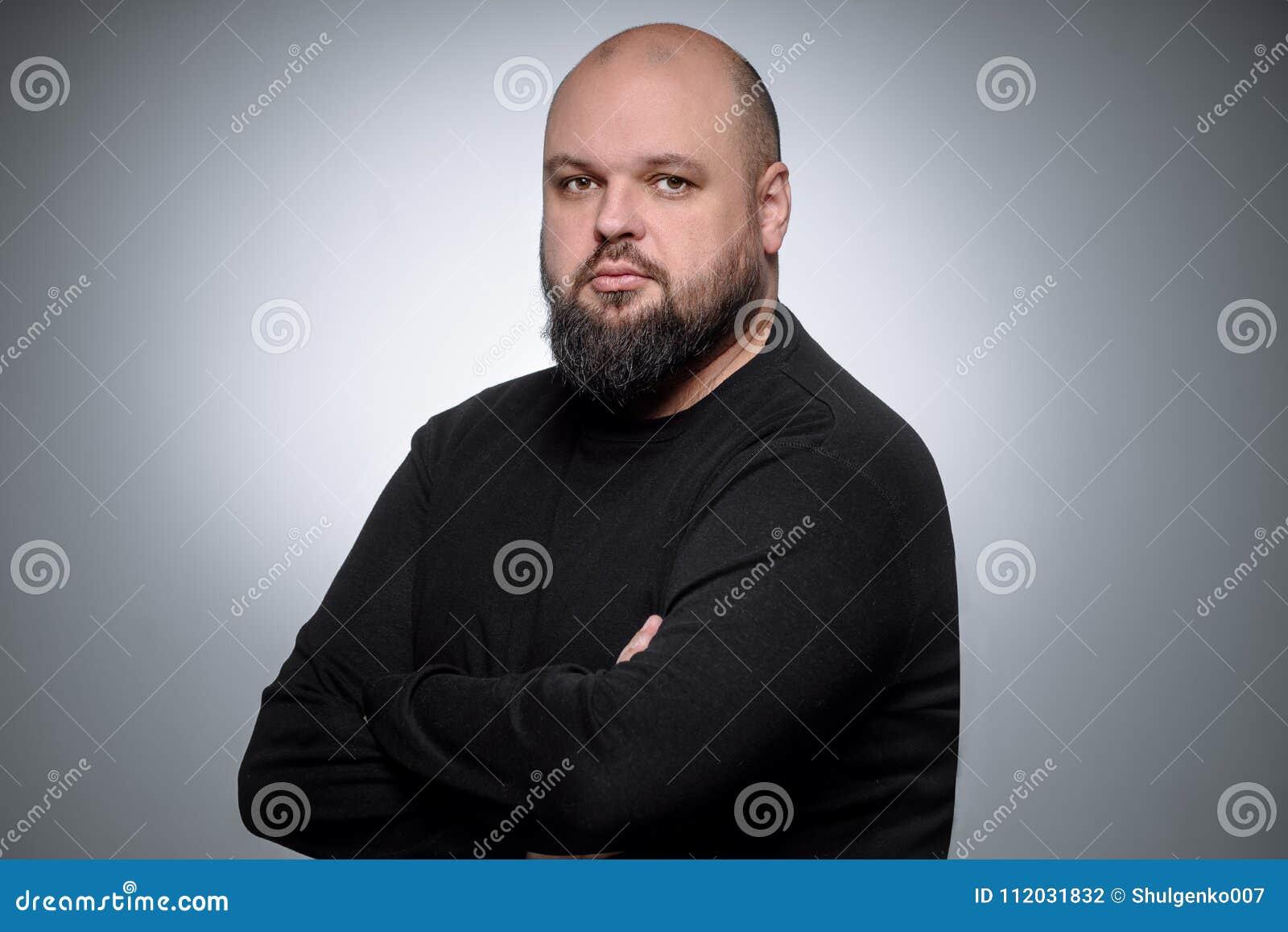 Studio strzelał gruby biznesmena główkowanie przeciw szaremu tłu Śliczny dorosły mężczyzna w czerń golfie Ekspresyjny portret