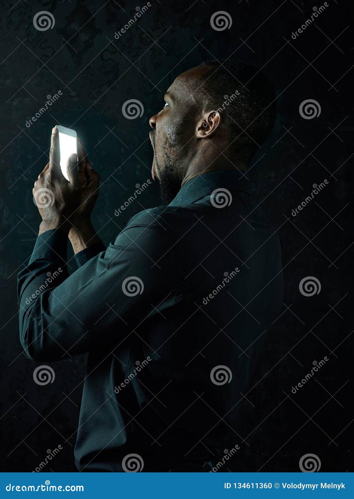 Studio tiré du jeune homme sérieux d africain noir pensant tout en parlant au téléphone portable sur le fond noir