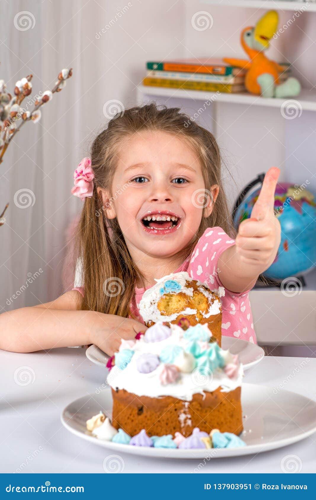 Studio van kleine meisjeszitting bij een lijst wordt geschoten en het eten van Pasen die Zij heeft een feestelijke stemming en ge