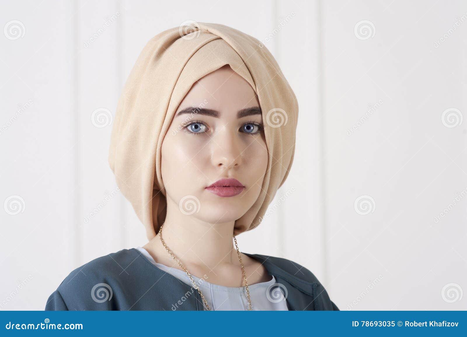 Studiofoto van een jong vrouwen oostelijk type in de moderne Moslimkleren en het mooie hoofddeksel