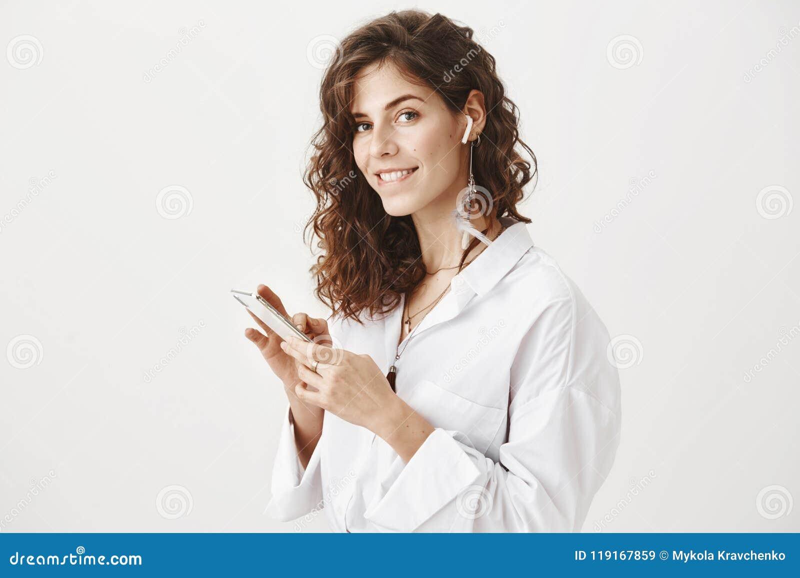 Studioporträt der heißen überzeugten Geschäftsfrau, die Smartphone und hörende Musik im drahtlosen Kopfhörer, beißende Lippe hält