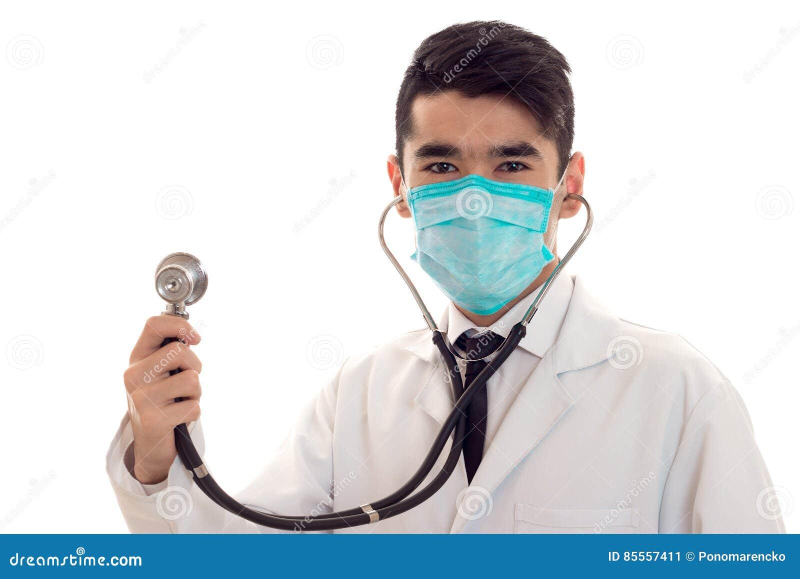 Studioporträt männlichen Doktors in der Uniform und in der Maske mit dem Stethoskop in seiner Handaufstellung lokalisiert auf wei