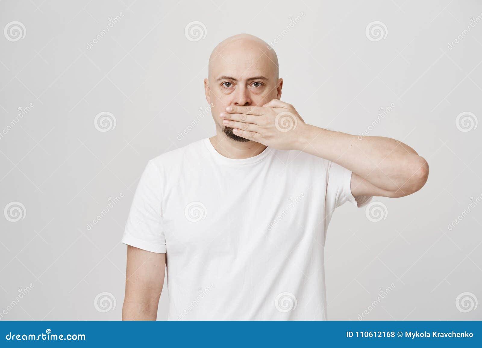 Studioportret die van ernstige kalme kale gebaarde mannelijke behandelende mond met hand en het bekijken camera, zich tegen grijs