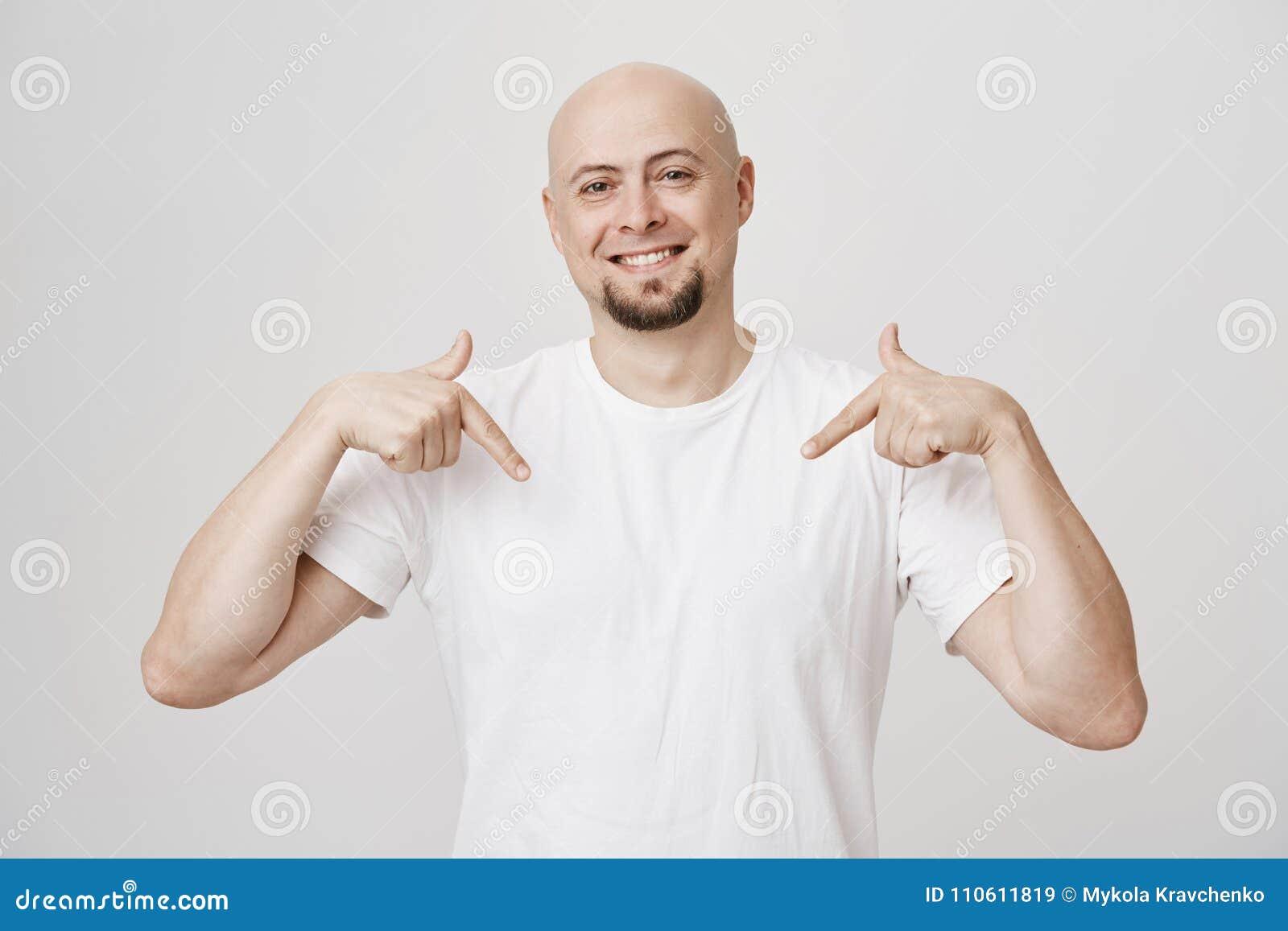 Studioportret van de vrolijke positieve kale Kaukasische gebaarde mens die neer met wijsvingers richten terwijl het glimlachen ru
