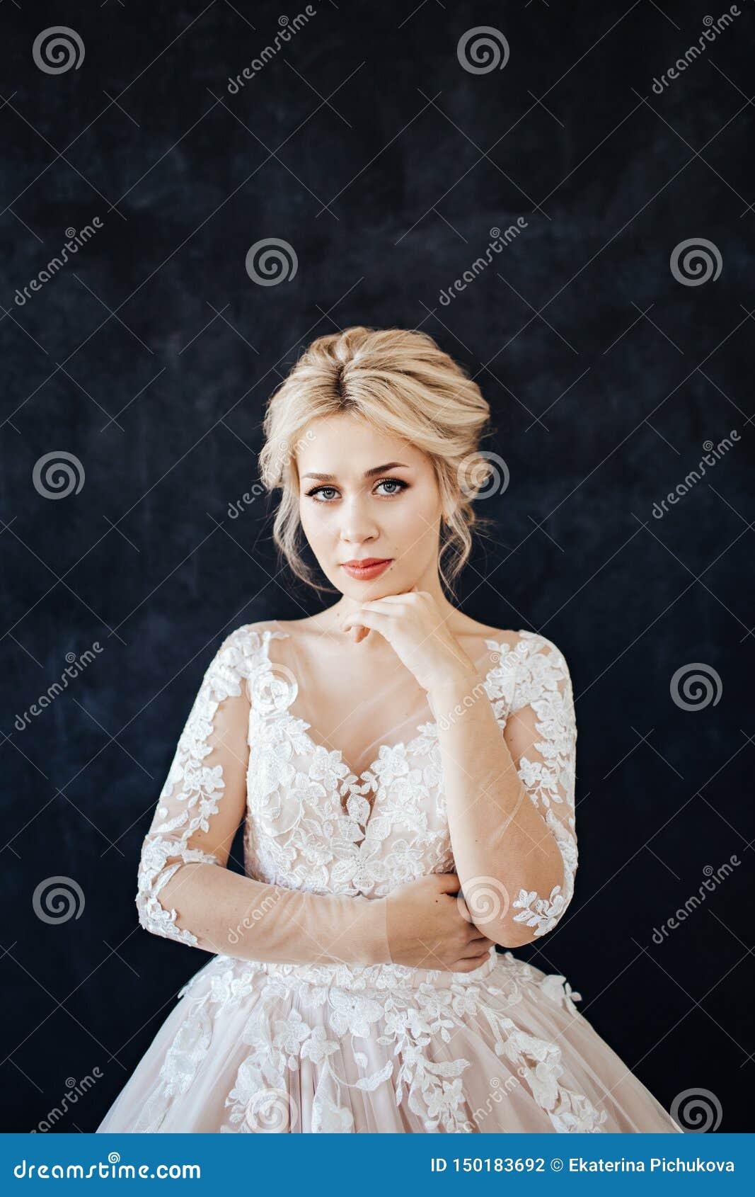Studioportret van een jong meisje van de bruid met professioneel huwelijksmake-up en kapsel