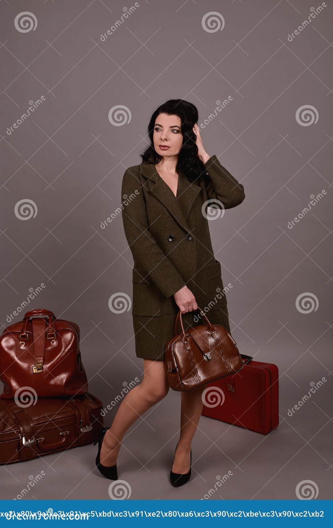 Studioportret van een vrouw in het klassieke laag stellen met reeks van retro koffers en handtas op een grijze achtergrond