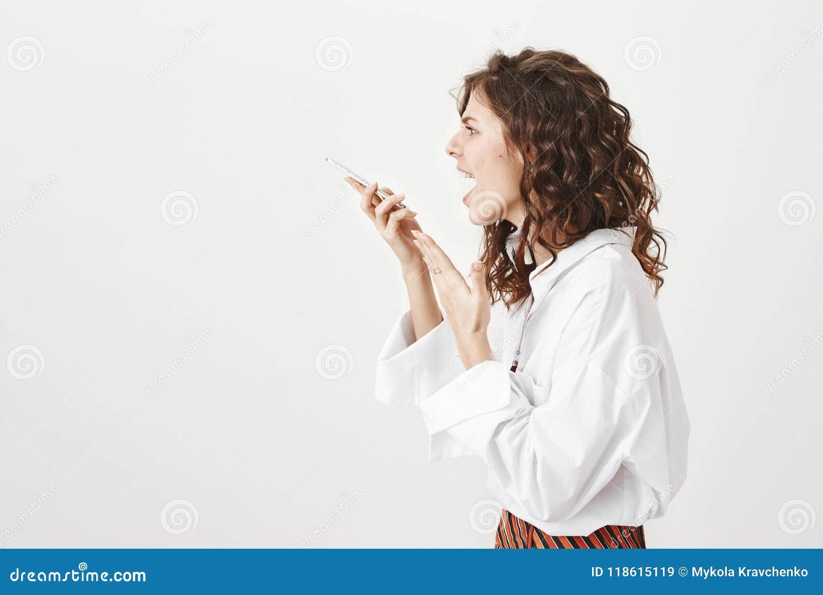 Studioportret van jonge in vrouw status in profiel die bij smartphone schreeuwen terwijl het houden van gadget in hand, het gestu
