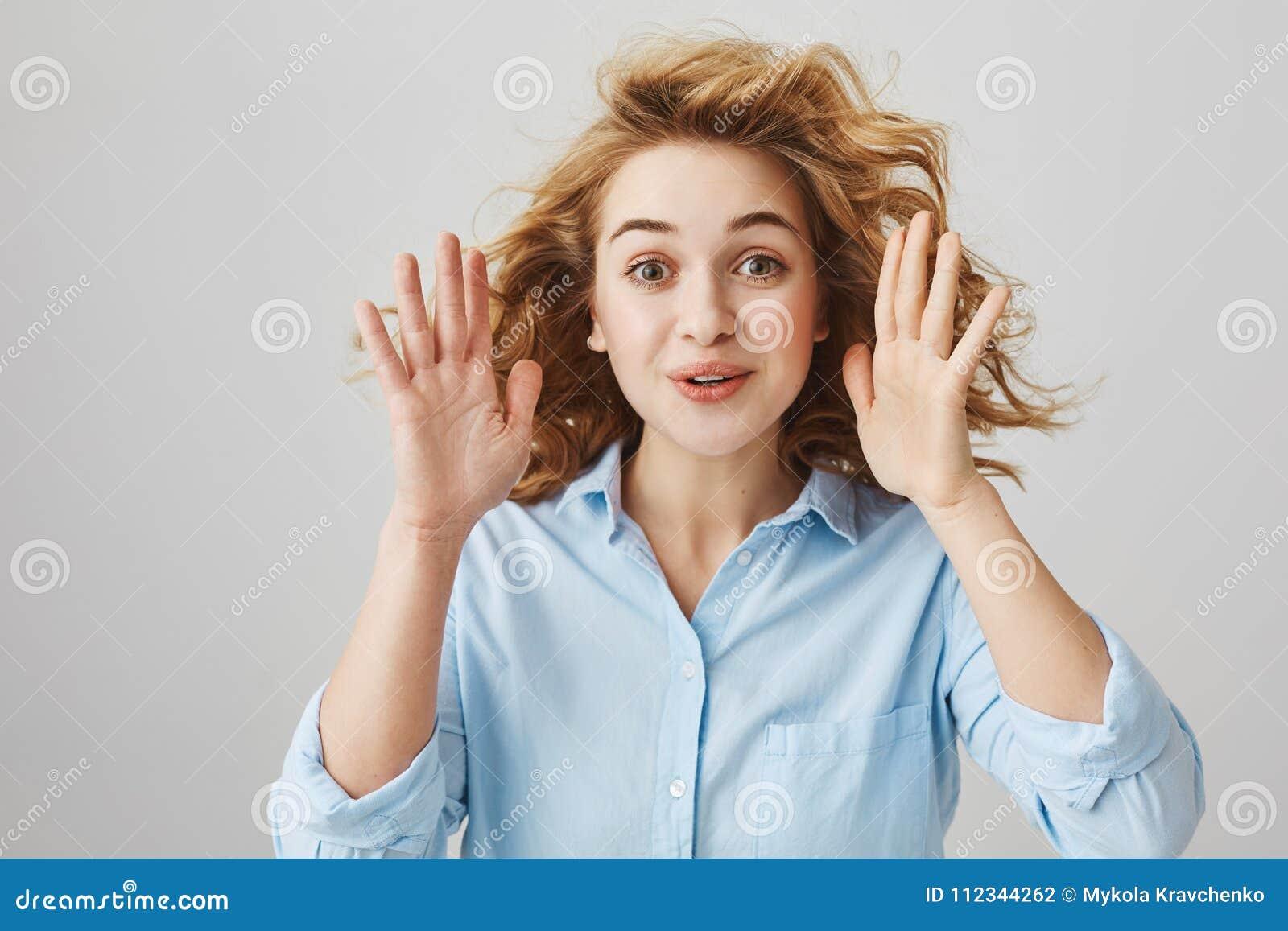 Studioportret van mooie grappige vrouw met krullend palmen opheffen dichtbij gezicht en haar die alsof weinig onderhoudend glimla