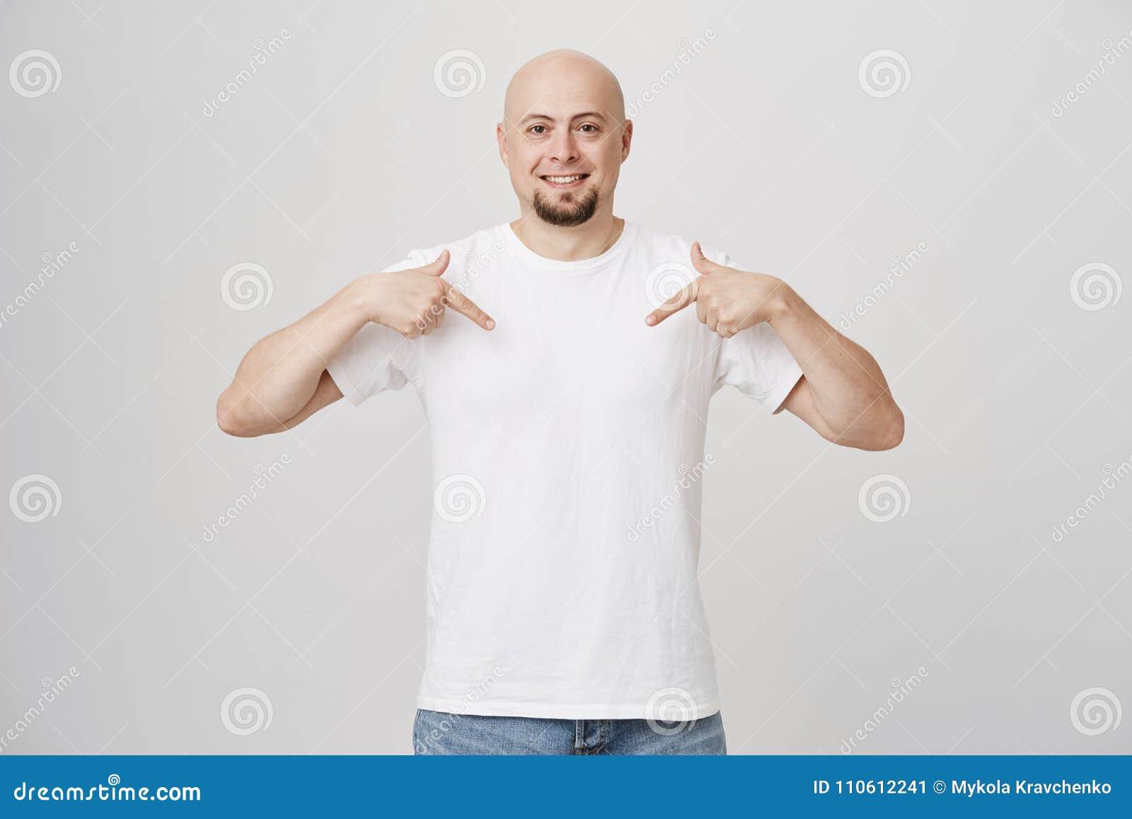 Studioportret van positief zeker kaal Europees mannetje met baard die op witte t-shirt richten of beneden met wijsvingers